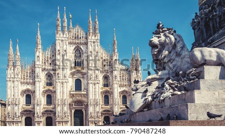 Sculpture of a lion and Milan Cathedral on the Piazza del Duomo in Milan, Italy. The Milan Cathedral (Duomo di Milano) in the background. It is the main tourist attraction of Milan.  #790487248
