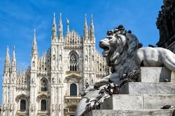 Sculpture of a lion in the Piazza del Duomo (Cathedral Square) in summer, Milan, Italy. The Milan Cathedral (Duomo di Milano) in the background. This place is the main tourist attraction of Milan.
