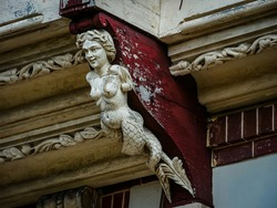 Sculpture of a mermaid decorating an old house