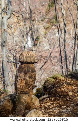 Sculpture of a mushroom on the trunk of a dead tree near the waterfall of Ray-pic in Ardèche