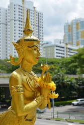 Sculpture of a Thai Kinnari overlooking a modern cityscape. In Southeast Asian mythology, Kinnaris are depicted as half-bird, half-woman creatures that can fly between the human and mystical worlds.