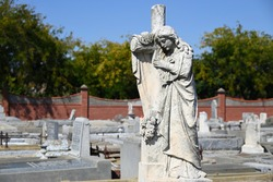 Sculpture of a woman mourning on the cross in a cemetery