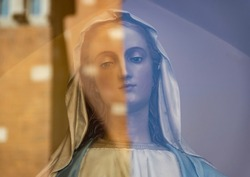 Sculpture of a woman with opposite colors reflected on the glass infront, dividing her in half