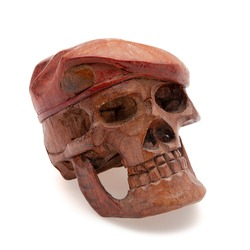 Sculpture of a wooden skull isolated in front of a white background