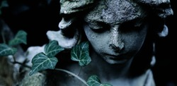 Sculpture of an angel with dark background. Antique statue.