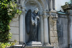 Sculpture of an Angel with flowers (roses) in her hand on a family tomb / crypt at the cemetery at Suedstern