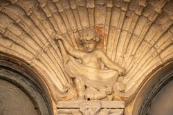 Sculpture of angel boy. Architectural ornament on the facade. Stone figure.