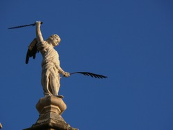 Sculpture of angel with pen and sword. On top of a roof you can see this white marble sculpture with bronze pen and sword. Granada, Spain