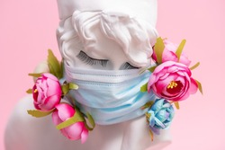 Sculpture of antique girl made of plaster in medical mask with flowers against coronavirus pandemic and common cold. Beauty salon fashion in pink background concept.