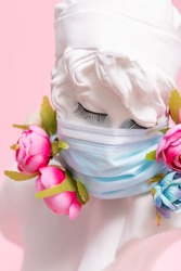 Sculpture of antique girl made of plaster in medical mask with flowers against pink background coronavirus pandemic COVID.