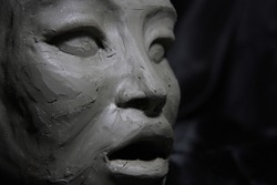Sculpture of asian woman, wet clay, face detail , on black background