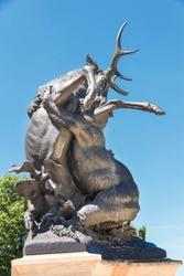 Sculpture of Bear attacking a deer in Polish park Swierklaniec.