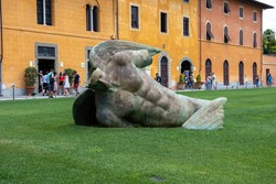 Sculpture of Fallen angel (Angelo caduto) on the lawn in the grass, Pisa, Italy