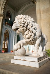 Sculpture of lion with a ball on a background of palace