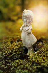 Sculpture of little girl in garden, background for Valentine's day. Selective focus and color toned.