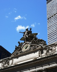 Sculpture of Mercury, the Roman god of travelers, atop Grand Central - seen against a blue sky with a cloud at his fingertip. The 14-foot Tiffany glass clock and name of the building are seen below.