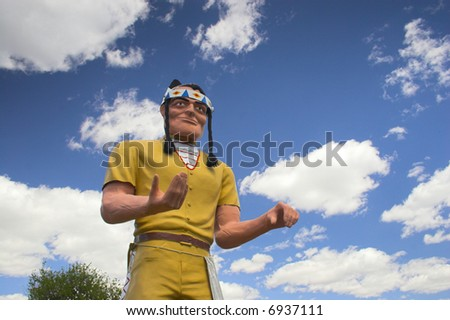 Sculpture of plastic Indian on the background of blue cloudy sky