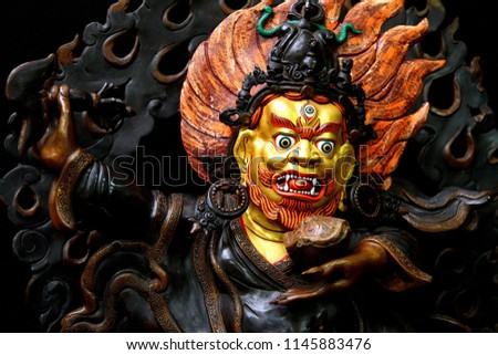 Sculpture of the two-armed Buddhist deity Mahakala on a black background.