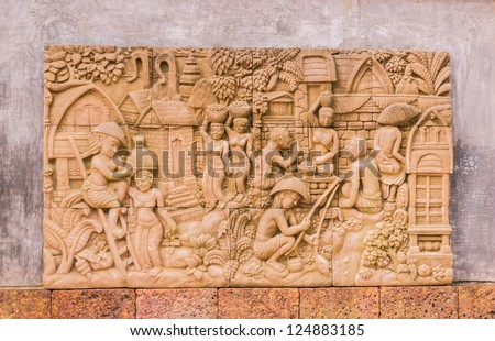 Sculpture on wall in garden. It is about way of life of Thai people in the past