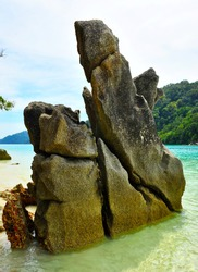 Sculpture texture rock on sea and sandy beach of Surin island background is scenery of mountain, clam blue sea, sky. Beauty of nature formation
