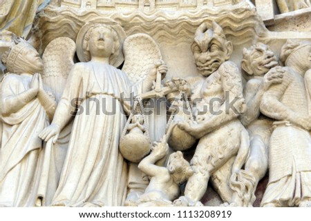 Sculptures depicting angels and demons weighing souls