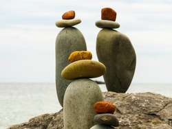 sculptures of balancing stones on a boulder by the sea