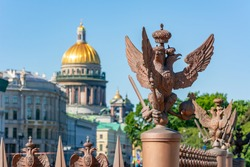 Sculptures of eagles at Alexander column on Palace square with St. Isaac's cathedral at background, Saint Petersburg, Russia