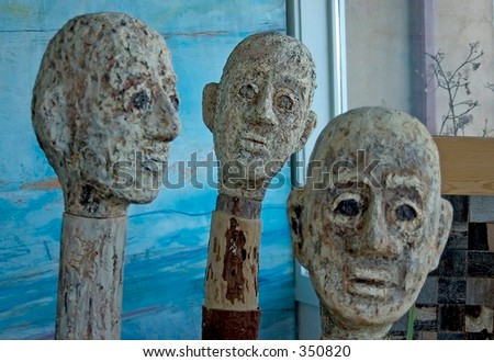 Sculptures of three abstract heads in an art gallery in northern New Mexico.