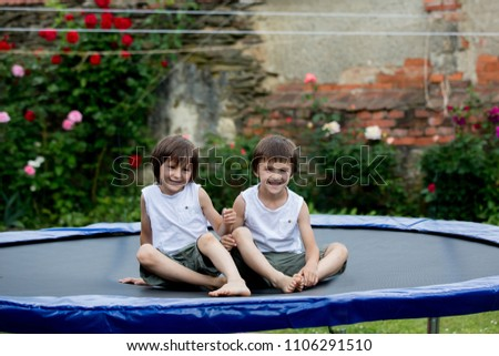 SCute children, brothers, jumping on a trampoline in garden, summertime