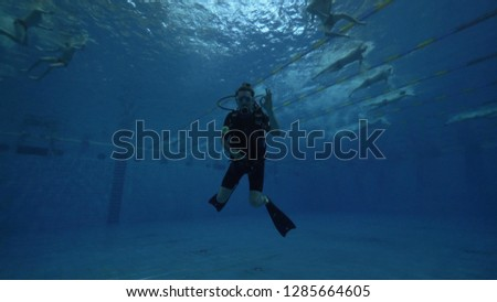 Sdiver in diving mask and diving equipment swimming underwater deep pool #1285664605