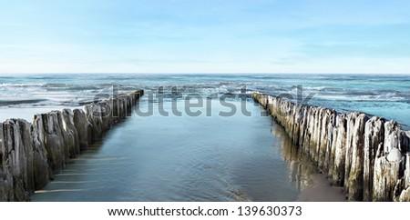 Sea and breakwater - stock photo