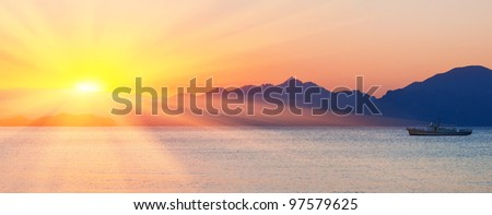 Sea and mountains against a sunset. Summer seascape.