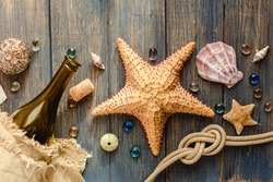 Sea and ocean gifts on a wooden background. Marine things. Sea products. Water Background for real  man captains and sailors. Pirate design. Bottle, rope, star. Underwater treasures.