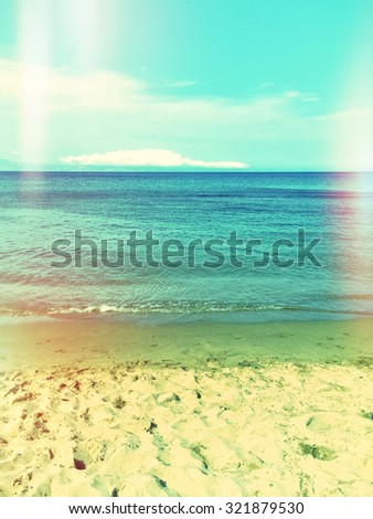 Sea and sand beach. Retro styled image with light leaks.