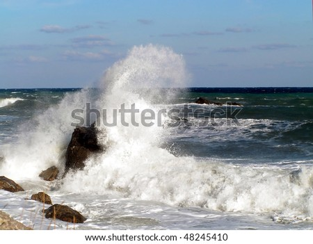 sea and shore in storm. waves crashing on the rocks on the shore - stock photo