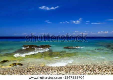 Sea background. Picturesque summer beach, pebbles in the surf line on a beautiful turquoise sea, Rhodes, Greece,  excursions, travel, recreation and vacation. space for text, text space #1347553904