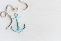 Sea background with anchor and marine rope on white wooden deck top view. Summertime sea background.