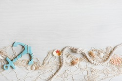 Sea background with fishing net, anchor and seashells top view on white wooden background. Summer sea holiday background.