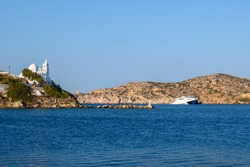 Sea bay and Greek church on the cliff, symbol of Ios island. Cyclades, Greece.