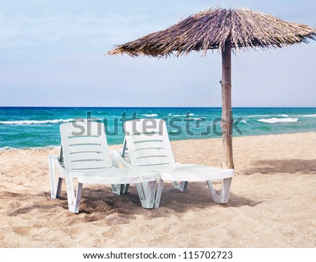 sea beach with the two beach beds and the beach umbrella - stock photo