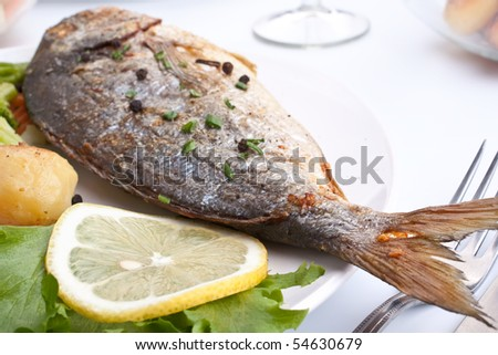 Sea Bream fish with vegetables on a white plate