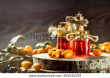 sea buckthorn oil in a small bottle with berries