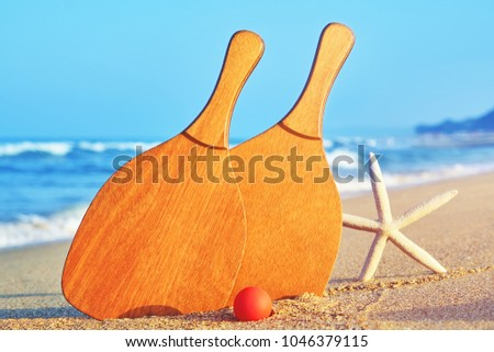 Sea coast in the tourist season. A starfish and a set for a game of beach tennis on the background of sea close-up. Wooden rackets and red ball in the sand