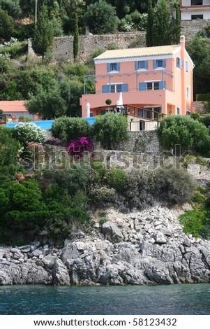 Sea coast of Corfu island. Photo made from coast line boat. Houses on shore.