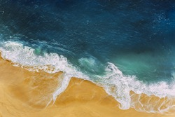 Sea coast, view from the height. Yellow sandy beach with blue sea. A deserted beach with a bird's-eye view. Sea waves roll on the sandy beach. Beautiful sea landscape. Ocean, waves, sand. Copy space