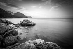 Sea coast with rocks and stones on long exposure. Dramatic black and white seascape.