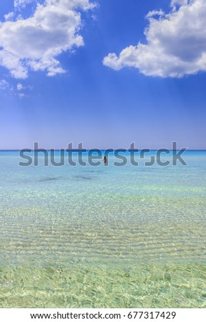 Sea colors of Italy.Summertime: relaxing at the nature.The most beautiful sandy beaches of Apulia: girl surrounded by turquoise crystalline water dominated by clouds,Salento coast, ITALY. (Taranto). #677317429
