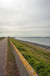 Sea dyke along the Haringvliet on the former Dutch island of Voorne-Putten in the province of South Holland. The dike has been raised with a low concrete wall due to the constantly rising water level.