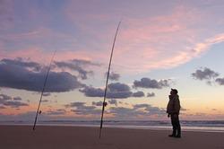 Sea fisherman waiting for fish at sunset. Surf fishing scene