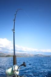 Sea fishing rod and reel over a beautiful seascape